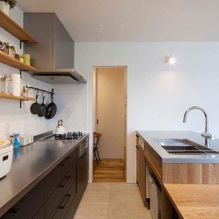 他の地域の中くらいの北欧スタイルのおしゃれなキッチン (一体型シンク、黒いキャビネット、ステンレスカウンター、白いキッチンパネル、セラミックタイルのキッチンパネル、シルバーの調理設備、磁器タイルの床、ベージュの床、フラットパネル扉のキャビネット) の写真