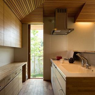 他の地域の中サイズのアジアンスタイルのおしゃれなキッチン (一体型シンク、インセット扉のキャビネット、中間色木目調キャビネット、人工大理石カウンター、白いキッチンパネル、シルバーの調理設備の、濃色無垢フローリング、茶色い床、白いキッチンカウンター) の写真
