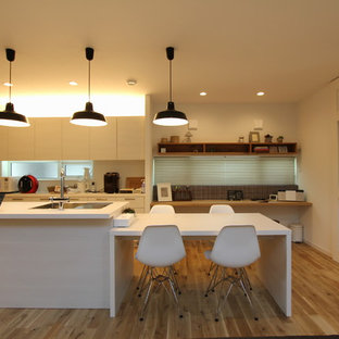 Country galley eat-in kitchen in Tokyo with an undermount sink, flat-panel cabinets, medium wood cabinets, onyx benchtops, stainless steel appliances, light hardwood floors, multiple islands and beige floor.