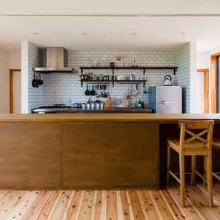 他の地域の中くらいのコンテンポラリースタイルのおしゃれなキッチン (アンダーカウンターシンク、オープンシェルフ、茶色いキャビネット、ステンレスカウンター、白いキッチンパネル、磁器タイルのキッチンパネル、シルバーの調理設備、無垢フローリング、アイランドなし、茶色い床) の写真