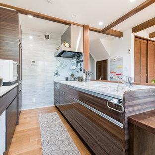 Cette photo montre une cuisine ouverte parallèle asiatique avec un évier intégré, un placard à porte plane, des portes de placard en bois sombre, un sol en bois brun, une péninsule et un sol marron.