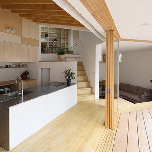 京都のモダンスタイルのおしゃれなキッチン (アンダーカウンターシンク、フラットパネル扉のキャビネット、淡色木目調キャビネット、ベージュキッチンパネル、白い調理設備、淡色無垢フローリング、ベージュの床) の写真