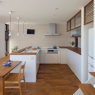 This is an example of a modern l-shaped eat-in kitchen in Other with beaded inset cabinets, white cabinets, solid surface benchtops, white splashback, porcelain splashback, stainless steel appliances, no island, brown benchtop, an integrated sink, medium hardwood floors and brown floor.