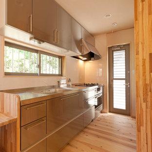 他の地域の中サイズのアジアンスタイルのおしゃれなI型キッチン (一体型シンク、フラットパネル扉のキャビネット、グレーのキャビネット、ステンレスカウンター、ガラスまたは窓のキッチンパネル、シルバーの調理設備の、淡色無垢フローリング、アイランドなし、ベージュの床、グレーのキッチンカウンター) の写真