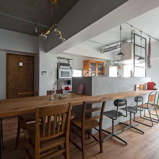 Offene, Kleine, Zweizeilige Moderne Küche mit braunem Holzboden, Glasfronten, orangefarbenen Schränken, Arbeitsplatte aus Holz, Küchengeräten aus Edelstahl, Kücheninsel, braunem Boden und brauner Arbeitsplatte in Osaka