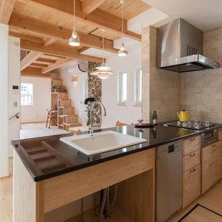 Idée de décoration pour une cuisine asiatique avec un évier posé, un placard avec porte à panneau encastré, des portes de placard en bois clair, un sol en bois clair, un îlot central et un sol beige.