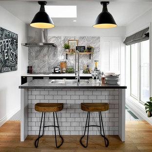 東京23区の中サイズのトラディショナルスタイルのおしゃれなキッチン (アンダーカウンターシンク、シェーカースタイル扉のキャビネット、白いキャビネット、ステンレスカウンター、グレーのキッチンパネル、セラミックタイルのキッチンパネル、パネルと同色の調理設備、セメントタイルの床、白い床) の写真