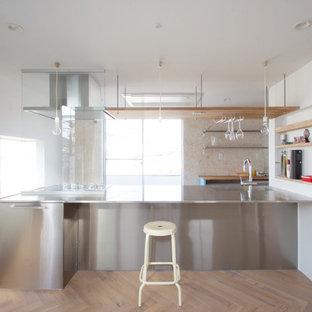 Ejemplo de cocina lineal, actual, con fregadero integrado, puertas de armario en acero inoxidable, encimera de acero inoxidable, suelo de madera pintada, una isla y suelo marrón