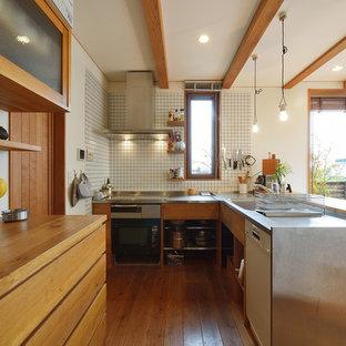 他の地域のおしゃれなキッチン (シングルシンク、フラットパネル扉のキャビネット、中間色木目調キャビネット、ステンレスカウンター、白いキッチンパネル、セラミックタイルのキッチンパネル、無垢フローリング、茶色い床、茶色いキッチンカウンター) の写真
