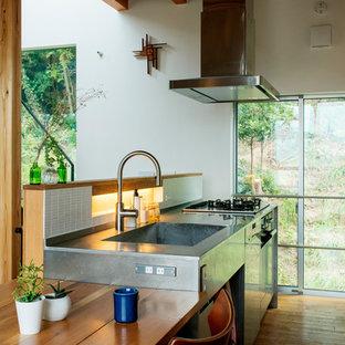 他の地域のコンテンポラリースタイルのおしゃれなI型キッチン (フラットパネル扉のキャビネット、ステンレスキャビネット、ステンレスカウンター、白いキッチンパネル、磁器タイルのキッチンパネル、茶色い床、一体型シンク、無垢フローリング、グレーのキッチンカウンター) の写真