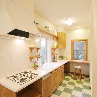 他の地域のカントリー風おしゃれなキッチン (ドロップインシンク、フラットパネル扉のキャビネット、中間色木目調キャビネット、白いキッチンパネル、マルチカラーの床) の写真