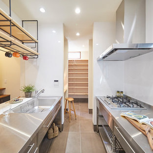 Industrial kitchen in Tokyo Suburbs with an integrated sink, flat-panel cabinets, stainless steel cabinets, stainless steel benchtops, a peninsula, grey floor and white benchtop.