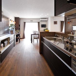 Cette image montre une cuisine ouverte parallèle asiatique avec un évier 1 bac, un placard à porte plane, des portes de placard noires, un plan de travail en inox, une crédence marron, un sol en bois brun, une péninsule et un sol marron.