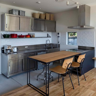 Diseño de cocina lineal, minimalista, de tamaño medio, abierta, con puertas de armario en acero inoxidable, encimera de acero inoxidable, salpicadero blanco, salpicadero de azulejos de cerámica, electrodomésticos de colores, una isla y encimeras grises