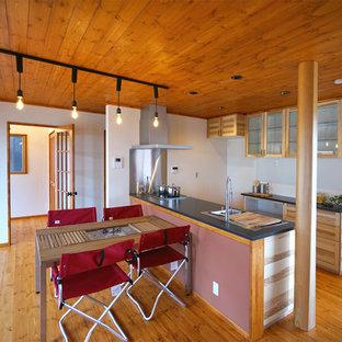 他の地域のカントリー風おしゃれなキッチン (シングルシンク、フラットパネル扉のキャビネット、淡色木目調キャビネット、無垢フローリング、茶色い床、御影石カウンター、黒いキッチンカウンター) の写真