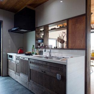他の地域, のインダストリアルスタイルのキッチンの写真 (シングルシンク、落し込みパネル扉のキャビネット、中間色木目調キャビネット、白いキッチンパネル、グレーの床)