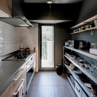 Idée de décoration pour une cuisine linéaire minimaliste fermée avec un évier intégré, un placard à porte affleurante, des portes de placard en bois clair, un plan de travail en inox, une crédence blanche, une crédence en mosaïque, un électroménager en acier inoxydable, un sol en vinyl, un sol gris et un plafond en papier peint.