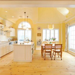 他の地域のヴィクトリアン調のおしゃれなキッチン (淡色無垢フローリング、ベージュの床、白いキャビネット、白いキッチンパネル、木材のキッチンパネル、白い調理設備、レイズドパネル扉のキャビネット) の写真