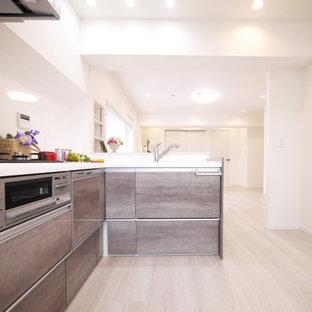 Foto de cocina en L, nórdica, abierta, con salpicadero blanco, suelo de contrachapado, una isla, suelo beige, encimeras blancas, papel pintado y puertas de armario con efecto envejecido
