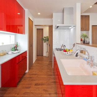 他の地域のコンテンポラリースタイルのおしゃれなキッチン (赤いキャビネット、無垢フローリング、茶色い床) の写真