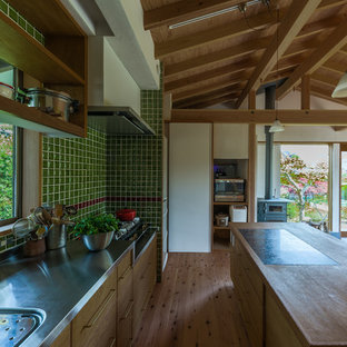 Asian single-wall kitchen in Other with an integrated sink, distressed cabinets, stainless steel benchtops, green splashback, porcelain splashback, medium hardwood floors, brown floor, flat-panel cabinets and with island.