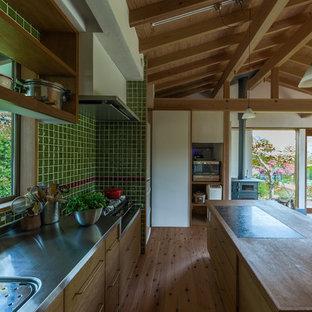 他の地域のアジアンスタイルのおしゃれなキッチン (一体型シンク、ヴィンテージ仕上げキャビネット、ステンレスカウンター、緑のキッチンパネル、磁器タイルのキッチンパネル、無垢フローリング、茶色い床、フラットパネル扉のキャビネット) の写真