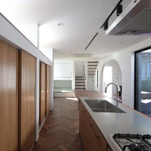 東京23区のモダンスタイルのおしゃれなアイランドキッチン (フラットパネル扉のキャビネット、濃色木目調キャビネット、ステンレスカウンター、グレーのキッチンカウンター、一体型シンク) の写真