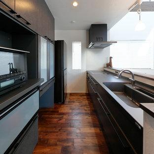 他の地域のモダンスタイルのおしゃれなペニンシュラキッチン (一体型シンク、フラットパネル扉のキャビネット、グレーのキャビネット、ステンレスカウンター、濃色無垢フローリング、茶色い床、ベージュのキッチンカウンター) の写真