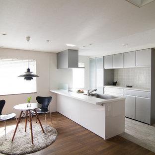 他の地域のモダンスタイルのおしゃれなキッチン (シングルシンク、フラットパネル扉のキャビネット、グレーのキャビネット、濃色無垢フローリング、茶色い床、白いキッチンカウンター) の写真