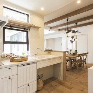 他の地域, のシャビーシック調のおしゃれなキッチン (一体型シンク、シェーカースタイル扉のキャビネット、白いキャビネット、ベージュキッチンパネル、無垢フローリング、茶色い床、白いキッチンカウンター) の写真