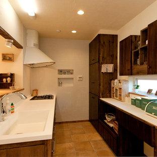 他の地域のおしゃれなキッチン (一体型シンク、フラットパネル扉のキャビネット、中間色木目調キャビネット、テラコッタタイルの床、茶色い床、茶色いキッチンカウンター) の写真