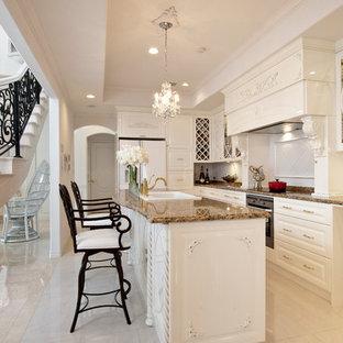 Foto di una cucina parallela vittoriana con lavello da incasso, ante con bugna sagomata, ante bianche, top in granito, pavimento in marmo, isola e pavimento beige