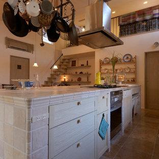 他の地域のカントリー風おしゃれなキッチン (インセット扉のキャビネット、淡色木目調キャビネット、タイルカウンター、シルバーの調理設備の) の写真
