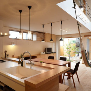 Inspiration för asiatiska linjära kök med öppen planlösning, med rostfria vitvaror, en integrerad diskho, släta luckor, vita skåp, ljust trägolv och en halv köksö
