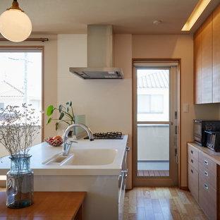 他の地域のアジアンスタイルのおしゃれなキッチン (一体型シンク、フラットパネル扉のキャビネット、中間色木目調キャビネット、ガラス板のキッチンパネル、シルバーの調理設備の、淡色無垢フローリング) の写真