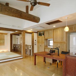 Ejemplo de cocina lineal, asiática, abierta, con fregadero bajoencimera, armarios con paneles lisos, puertas de armario de madera clara y suelo de contrachapado
