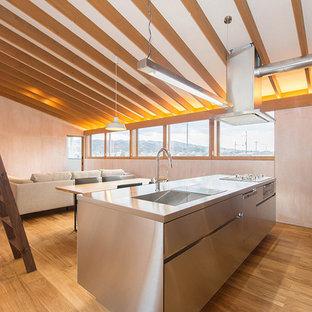 他の地域のアジアンスタイルのおしゃれなアイランドキッチン (シングルシンク、フラットパネル扉のキャビネット、ステンレスキャビネット、ステンレスカウンター、無垢フローリング、茶色い床) の写真