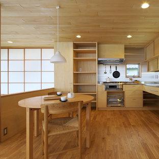 他の地域の中サイズのアジアンスタイルのおしゃれなキッチン (フラットパネル扉のキャビネット、中間色木目調キャビネット、ソープストーンカウンター、メタリックのキッチンパネル、シルバーの調理設備の、無垢フローリング、ベージュの床、シングルシンク) の写真