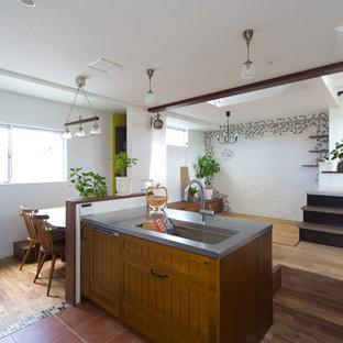 京都の地中海スタイルのおしゃれなアイランドキッチン (シングルシンク、中間色木目調キャビネット、ステンレスカウンター、テラコッタタイルの床、赤い床) の写真