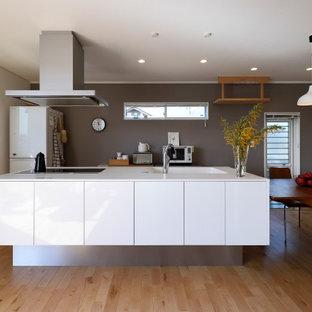 Imagen de cocina lineal, contemporánea, abierta, con encimera de acrílico, salpicadero blanco, suelo de madera en tonos medios, una isla, suelo marrón, encimeras blancas y papel pintado
