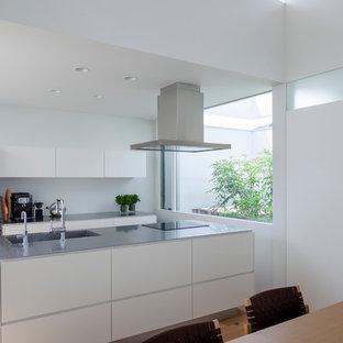 他の地域のコンテンポラリースタイルのおしゃれなキッチン (シングルシンク、フラットパネル扉のキャビネット、白いキャビネット、ステンレスカウンター、白い調理設備、淡色無垢フローリング、茶色い床) の写真