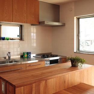 東京都下のモダンスタイルのおしゃれなキッチン (一体型シンク、フラットパネル扉のキャビネット、中間色木目調キャビネット、ステンレスカウンター、白いキッチンパネル、シルバーの調理設備の) の写真