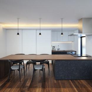 他の地域のコンテンポラリースタイルのおしゃれなキッチン (フラットパネル扉のキャビネット、黒いキャビネット、木材カウンター、白いキッチンパネル、濃色無垢フローリング、茶色い床、茶色いキッチンカウンター) の写真