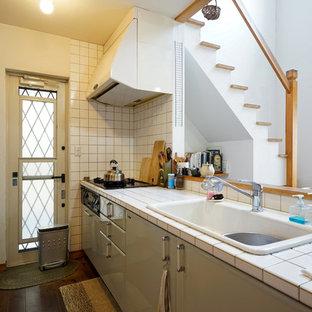 他の地域の北欧スタイルのおしゃれなキッチン (ドロップインシンク、フラットパネル扉のキャビネット、緑のキャビネット、タイルカウンター、白いキッチンパネル、セラミックタイルのキッチンパネル、濃色無垢フローリング、茶色い床) の写真