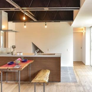 他の地域のコンテンポラリースタイルのおしゃれなキッチン (アンダーカウンターシンク、フラットパネル扉のキャビネット、中間色木目調キャビネット、白いキッチンパネル、淡色無垢フローリング、ベージュの床、白いキッチンカウンター) の写真