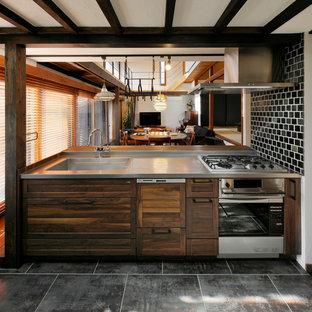 Offene Asiatische Küche mit Waschbecken, Schrankfronten mit vertiefter Füllung, hellbraunen Holzschränken, Edelstahl-Arbeitsplatte, Halbinsel und grauem Boden in Sonstige