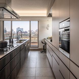 東京23区のモダンスタイルのおしゃれなキッチン (アンダーカウンターシンク、インセット扉のキャビネット、濃色木目調キャビネット、シルバーの調理設備、セラミックタイルの床、グレーの床、黒いキッチンカウンター) の写真