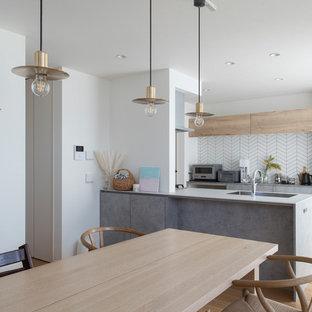 コンテンポラリースタイルのおしゃれなキッチン (アンダーカウンターシンク、インセット扉のキャビネット、グレーのキャビネット、白いキッチンパネル、シルバーの調理設備、無垢フローリング、茶色い床、グレーのキッチンカウンター) の写真