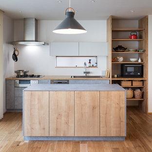 北欧スタイルのおしゃれなアイランドキッチン (シルバーの調理設備の、シングルシンク、フラットパネル扉のキャビネット、グレーのキャビネット、木材カウンター、淡色無垢フローリング) の写真