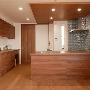 東京23区のモダンスタイルのおしゃれなキッチン (アンダーカウンターシンク、インセット扉のキャビネット、中間色木目調キャビネット、青いキッチンパネル、サブウェイタイルのキッチンパネル、シルバーの調理設備、茶色い床、茶色いキッチンカウンター) の写真